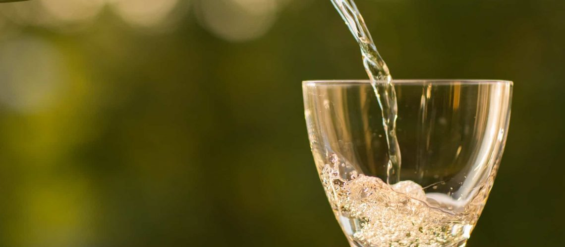 Weißwein wird in ein Glas eingeschenkt